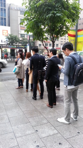 People waiting for the bus in line. Line up and be patient!